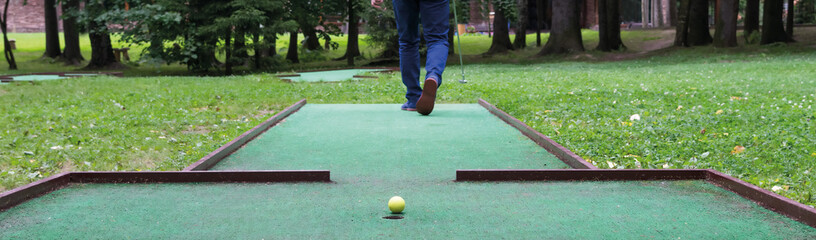 mini-golf player goes for a kick, close-up
