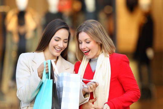 Happy shoppers checking purchases in a shooping bag