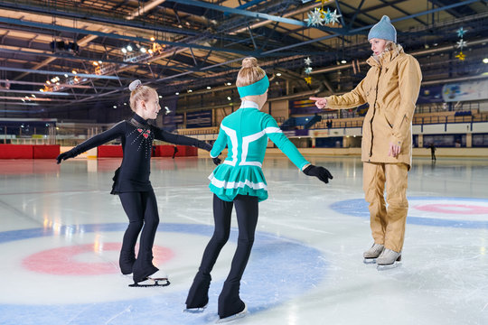 Full  length portrait of woman coach  training  two little girls figure skating in indoor rink