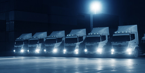 New truck fleet in the container depot at night in blue tone for transportation industry logistics background.