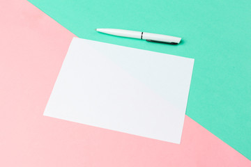 White paper notepad on pastel color background.Flat lay design.