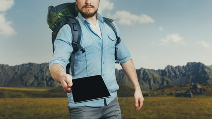 Unrecognizable man traveler with backpack holds a digital tablet. The concept of information assistance in travel and tourism