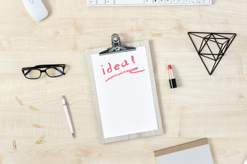 feminine workspace clipboard word idea written red lipstick and accessories flat lay top view