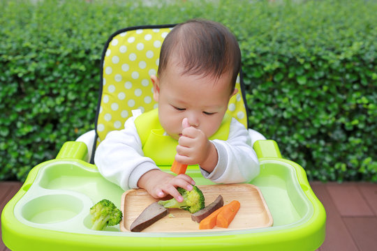 Asian infant baby boy eating by Baby Led Weaning (BLW). Finger foods concept.