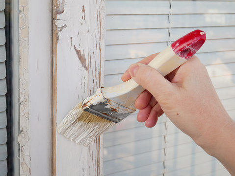 hand hold brush and painting the window