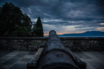 Old cast canon overlooking sea shot in sunset