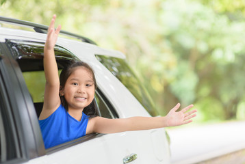 Happy kid with raised arms from window car