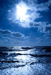 A deep blue sea glistening white and a big deep blue sky with the sun shining brightly through the clouds