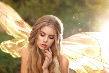 gorgeous young enchantress with transparent wings and blond hair with beautiful appearance, model posing with closed eyes, cool summer photo, fairytale hero with bare shoulders in the sun