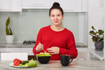 Brunette future mother has healthy lunch, eats fresh vegetable salad, drinks tea, sits at modern kitchen, keeps hand on belly, wears red loose sweater, being at home. Pregnancy and nutrition concept