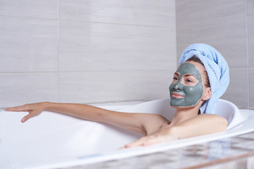 Portrait of a woman in facial alginate mask lying in the retro bath in the bathroom