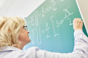 Dozentin schreibt Formel an die Tafel