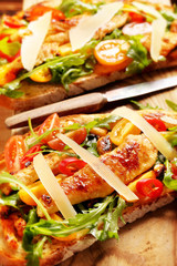 Chicken sandwich on fresh bread with arugula tomato and cheese