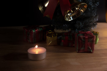 Group of gift box with candle under christmas tree in christmas night concept on wooden table.