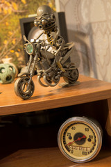 Bike and motorcyclist - a toy standing on the shelf