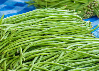 Cow peas or Yard long bean (Vigna unguiculata subsp. sesquipedalis). Pile of Thai Long Beans for sale in vegetable local market of Thailand ,generally called Tua-Paak-Yao. - Selective focus.