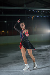 An ice skater is skating in a circle. She is enjoying her performance.