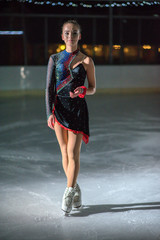 This young ice skater's movement is brilliant. She performs beautifully.