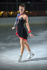 A young lady makes different poses during her routine on the ice.