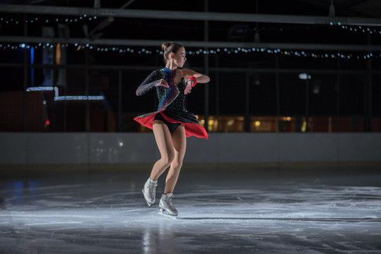 A beautiful ice skater during her performance on the ice. She is wearing a gorgeous costume.