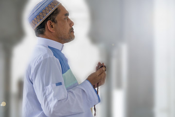 Middle age muslim man praying at mosque.