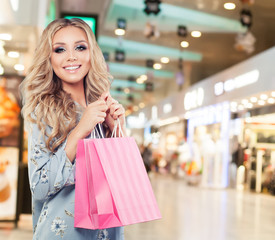Pretty woman with present in shopping mall