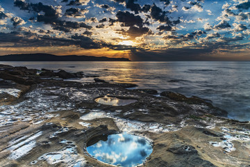 Sunrise Seascape with Clouds and Reflections in the Rock Pool