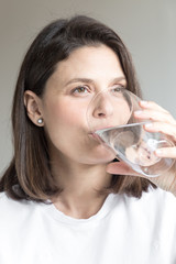 Beautiful charming woman drinking a big glass of water and wearing white clothes