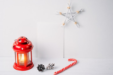 Red lantern with a candle, pine cones, star and empty white sheet on a white background. Christmas decoration