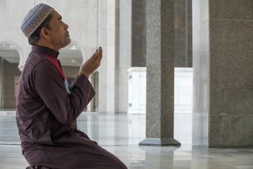 Middle age muslim man praying at mosque.