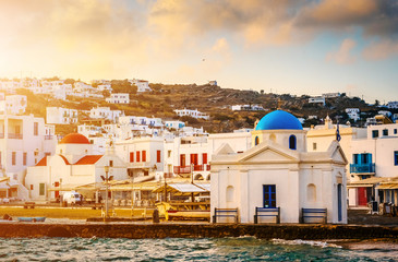 Colourful seafront with greek churches of Mykonos at sunset, view from the sea