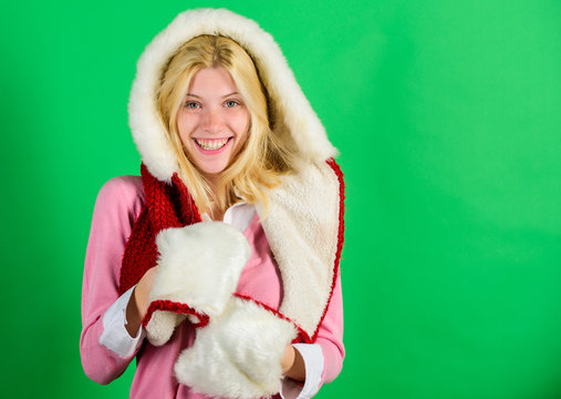 Woman emotional face posing in warm furry hood. Girl cheerful blonde warming up wear fur hood on green background. Winter time for cozy warm accessories. Lets stay warm in fur clothing