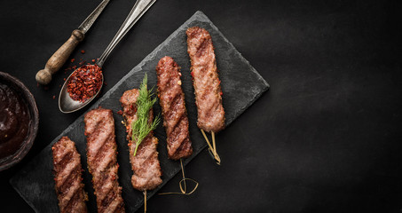 Grilled kebab with spices and sauce on a dark background