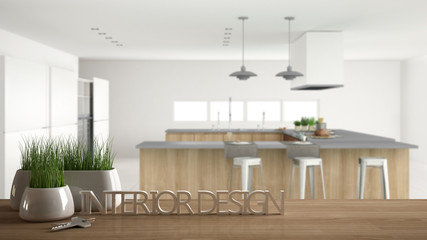Wooden table, desk or shelf with potted grass plant, house keys and 3D letters making the words interior design, over professional modern kitchen, project concept copy space background