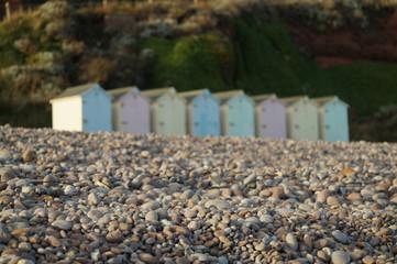 Pastel coloured beach huts on shingle beach