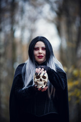 Portrait of witch girl in black cloak with skull