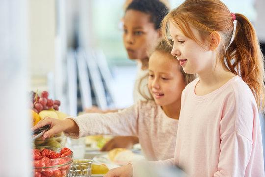 Schüler in Grundschule nehmen Obst vom Büffet