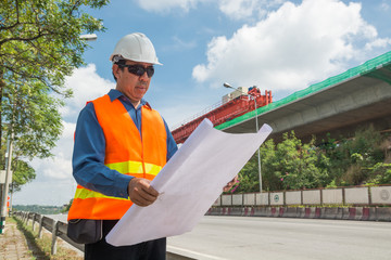 Engineer or Architect wear white Helmet working or reading Construction Plan