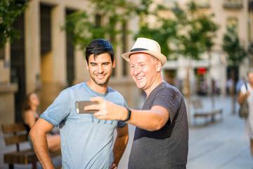 Two male friends taking selfie using smartphone