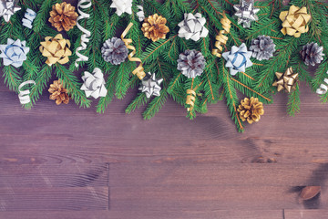 Christmas composition with copy space. On a wooden background, spruce branches spread out. Golden bows, cones and ribbons decorate the composition.