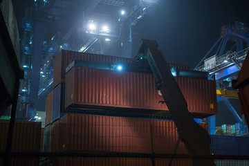 Reach Stacker during operation. Reach-stacker container loader during night work. Industrial port container terminal