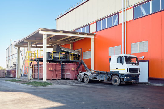 At modern waste recycling plant yard, process of loading sorted garbage from conveyor belt into container for further transportation by truck recycling or disposal