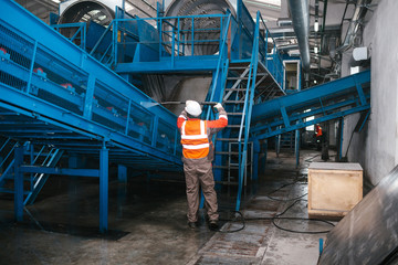 The worker washes the equipment at the waste sorting plant. Waste processing plant. Technological process.