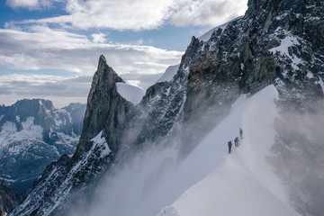 Obraz Climbers or alpinist on a knife sharp ridge of an alpine peak or summit of Aiguille du Rochefort. Alpine landscape and adventure climbing ascent in Mont Blanc Massif. Alpinism in high mountains. - fototapety do salonu