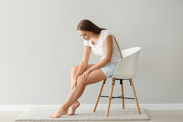 Woman suffering from pain in leg while sitting on chair near light wall