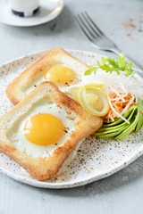 American breakfast on a plate with fried eggs in toast, with tomatoes, fresh daikon, carrots, arugula and espresso. Fried egg for traditional breakfast close up shoot