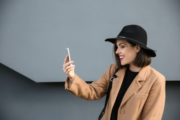 Beautiful fashionable woman with mobile phone near grey wall outdoors