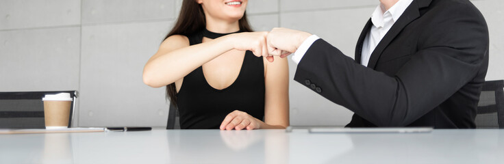 Businesswoman and Businessman in black suits are making fits bump.