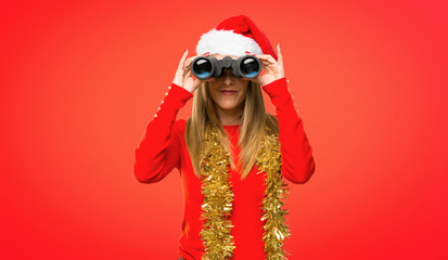 Blonde woman dressed up for christmas holidays and looking for something in the distance with binoculars on red background
