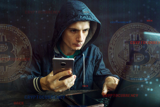 Hacker with a face is trying to steal cryptocurrency using a computer. Fraud at Cryptojacking